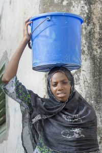Afro beauty carrying a bucket of water in a slug
